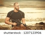 muscle man armed with automatic ... | Shutterstock . vector #1207123906