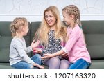 laughing mother sitting on the... | Shutterstock . vector #1207163320