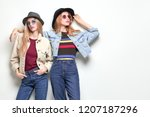two fashionable girl posing in... | Shutterstock . vector #1207187296
