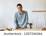 cheerful bearded male carpenter ... | Shutterstock . vector #1207246366