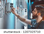 young brewer adjusts... | Shutterstock . vector #1207325710