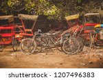 Small photo of Parked bicycle rickshaws in india, multitude of rickshaws in red color and bicycles waiting to be used on a gravel parking lot.