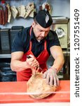 male butcher boning a ham in a... | Shutterstock . vector #1207551409