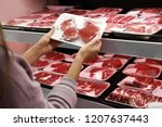 woman taking packed pork meat... | Shutterstock . vector #1207637443