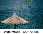 reed sunshade beside the sea | Shutterstock . vector #1207703083