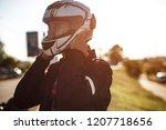 a biker put on his helmet.... | Shutterstock . vector #1207718656