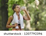 Small photo of Beautiful young woman drinking water and cooling off after her running training at the park
