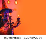 Small photo of Time for horror. 31 october. Bearded man with a clock utters a spell. Scary face man. Halloween decoration and scary concept for daddy