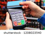 hand of woman paying with... | Shutterstock . vector #1208023540