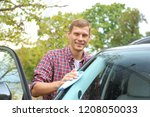 man washing car windshield with ... | Shutterstock . vector #1208050033