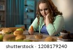 sad fat girl eating carrot and... | Shutterstock . vector #1208179240