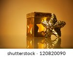 Golden glamour theme with sparkling christmas star and handmade candle holder over light brown background. Studio shot - stock photo