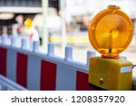 Small photo of Construction site and safety. Street barricade with warning signal lamp on a road, blur site background