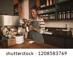 smiling young african barista... | Shutterstock . vector #1208583769