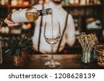 Stock photo close up shot of a bartender pouring white wine into a glass hospitality beverage and wine 1208628139