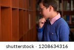 cute schoolboy chooses a book... | Shutterstock . vector #1208634316