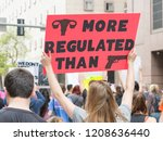 Stock photo a protester holds sign uterus more regulated than guns at the march for our lives rally 1208636440