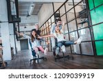 cheerful young colleagues... | Shutterstock . vector #1209039919