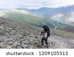 man with a backpack climbing... | Shutterstock . vector #1209105313