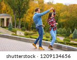 Small photo of Happy young couple dancing in autumn park