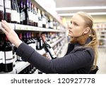 young woman is choosing wine in ...   Shutterstock . vector #120927778