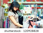 young elegant woman shopping in clothes store - stock photo