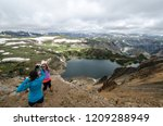 Two female friends (20s) take pictures of each other at an overlook along Montana Beartooth Pass Highway in the Rocky Mountains