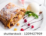 Small photo of Apple strudel with vanilla ice cream and mint and berries on white plate, close up