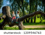 two boys are sitting on a log.... | Shutterstock . vector #1209546763