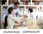 focused female employee point... | Shutterstock . vector #1209564139