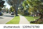Small photo of Quiet street scene of the sidewalk and idyllic homes in a suburban neighborhood