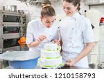 two pastry bakers decorating... | Shutterstock . vector #1210158793