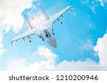 Combat fighter jet on a military mission with weapons - rockets, bombs, weapons on wings, with fire afterburner engine nozzles, flies in clouds - stock photo