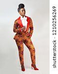 Small photo of Confident African business woman wearing an African print suit and red heels with a sophisticated hair style standing in a clean space with her hand in her pocket