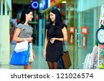smiling female friends shopping in the city mall - stock photo