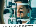 ophthalmologist examining boy... | Shutterstock . vector #1210317373