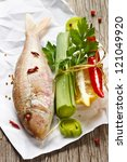 Fresh fish and fresh vegetables on a wooden board. - stock photo