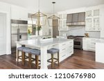 Stock photo beautiful white kitchen in new luxury home features large island pendant lights and hardwood 1210676980