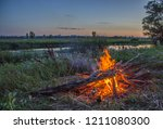 a bonfire with a city in the... | Shutterstock . vector #1211080300
