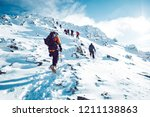 Small photo of A group of climbers ascending a mountain in winter