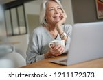 elderly woman at home with... | Shutterstock . vector #1211172373