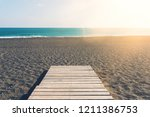 Small photo of wooden gangplank on beach against sea and blue sky on sunny day