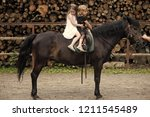 children sit in rider saddle on ... | Shutterstock . vector #1211545489