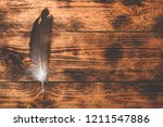 hawk feather over old wooden... | Shutterstock . vector #1211547886