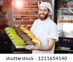 young cute baker in white... | Shutterstock . vector #1211654140