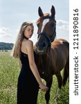 girl rider stands next to the... | Shutterstock . vector #1211890816