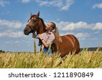 girl rider stands next to the... | Shutterstock . vector #1211890849