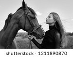 girl rider stands next to the... | Shutterstock . vector #1211890870