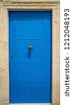 aged blue door in andalusian... | Shutterstock . vector #1212048193