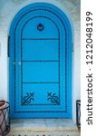 aged blue door in andalusian... | Shutterstock . vector #1212048199